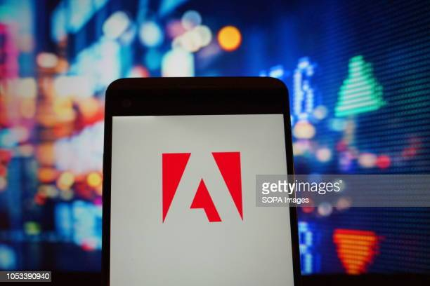 In this photo illustration the logo of Adobe is seen displayed on a smartphone