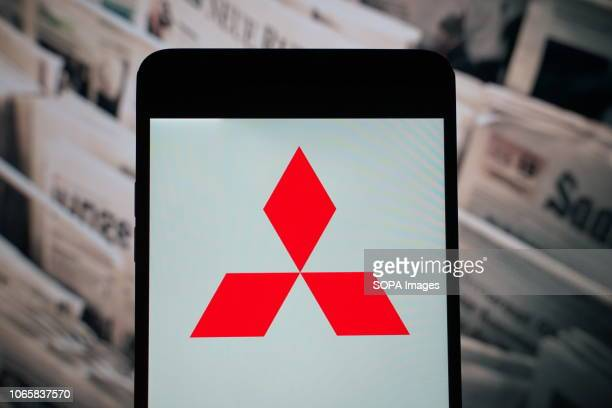 In this photo illustration the logo of Mitsubishi is seen displayed on a smartphone