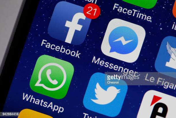 In this photo illustration the logo of the Facebook Messenger Whatsapp and Twitter applications are displayed on the screen of an Apple iPhone on...