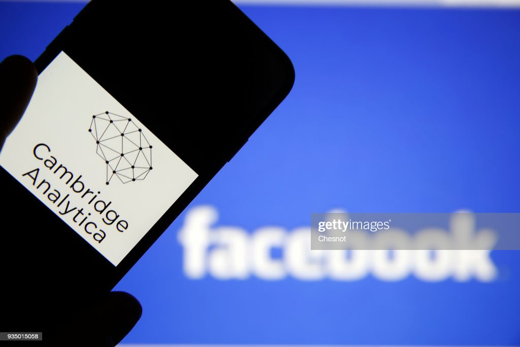 In this photo illustration the logo of the strategic communication company 'Cambridge Analytica' is seen on the screen of an iPhone in front of a computer screen showing a Facebook logo on March 20, 2018 in Paris, France. Cambridge Analytica is accused of collecting the personal information of 50 million users of the Facebook social network without their consent and would have used it to develop software to predict and influence voter voting during the campaign American election according to the New York Times and the Guardian. Facebook share price fell by more than 5% Monday shortly after the opening of Wall Street. (