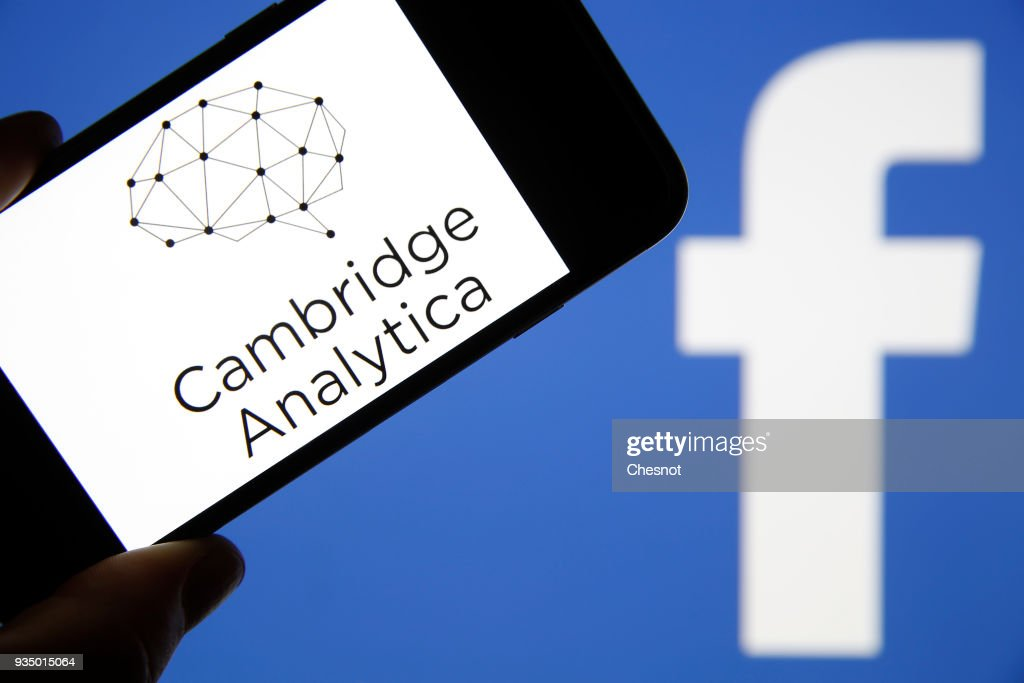 In this photo illustration the logo of the strategic communication company 'Cambridge Analytica' is seen on the screen of an iPhone in front of a computer screen showing a Facebook logo on March 20, 2018 in Paris, France. Cambridge Analytica is accused of collecting the personal information of 50 million users of the Facebook social network without their consent and would have used it to develop software to predict and influence voter voting during the campaign American election according to the New York Times and the Guardian. Facebook share price fell by more than 5% Monday shortly after the opening of Wall Street.