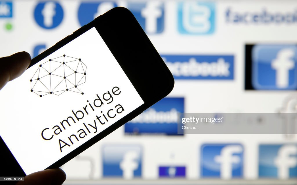 In this photo illustration the logo of the strategic communication company 'Cambridge Analytica' is seen on the screen of an iPhone in front of a computer screen showing Facebook logos on March 20, 2018 in Paris, France. Cambridge Analytica is accused of collecting the personal information of 50 million users of the Facebook social network without their consent and would have used it to develop software to predict and influence voter voting during the campaign American election according to the New York Times and the Guardian. Facebook share price fell by more than 5% Monday shortly after the opening of Wall Street. (