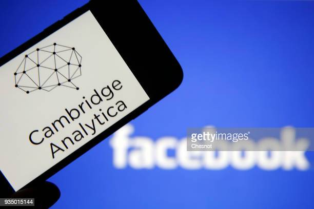 In this photo illustration the logo of the strategic communication company 'Cambridge Analytica' is seen on the screen of an iPhone in front of a...