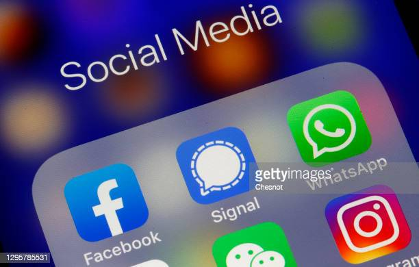 In this photo illustration, the logos of social media applications, Facebook, Signal and WhatsApp are displayed on the screen of an iPhone on January...
