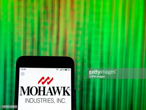 In this photo illustration the Mohawk Industries Commercial company logo seen displayed on a smartphone
