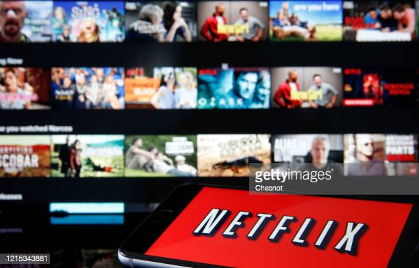In this photo illustration, the Netflix media service provider's logo is displayed on the screen of an iPhone in front of a television screen on...