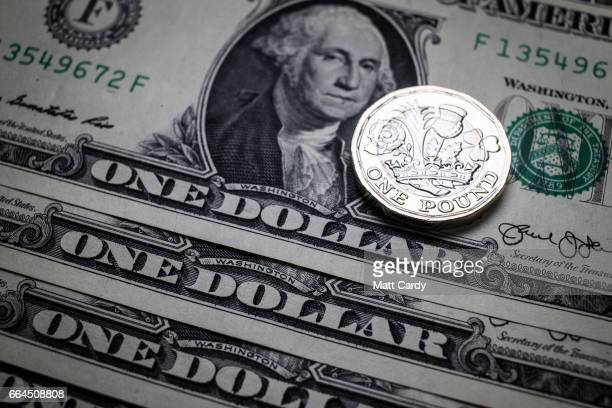 In this photo illustration the new £1 pound coin is seen alongside US dollar bills on April 4 2017 in Bath England Currency experts have warned that...