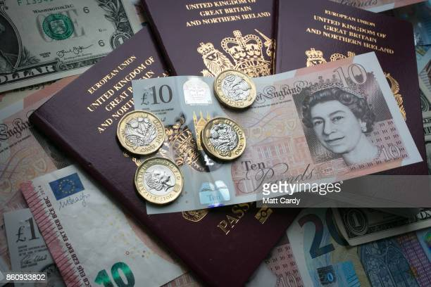 In this photo illustration, the new £10 note is placed on British passports alongside US dollar bills and euro notes on October 13, 2017 in Bath,...