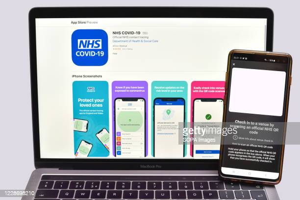 In this photo illustration the NHS Test and Trace app which has been launched in England and Wales is displayed on a smartphone with a laptop on the...