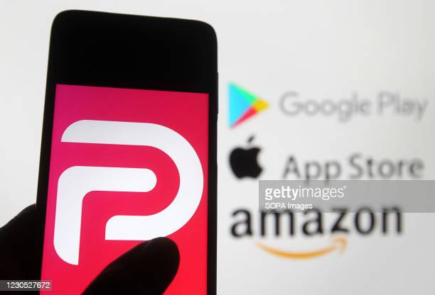 In this photo illustration the Parler logo seen displayed on a smartphone with the Google play, Amazon and Apple logos displayed on PC screen in the...