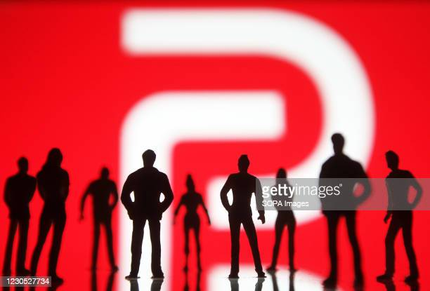 In this photo illustration the Parler logo seen in front of the silhouettes of toy people. Google, Apple and Amazon have suspended the social...