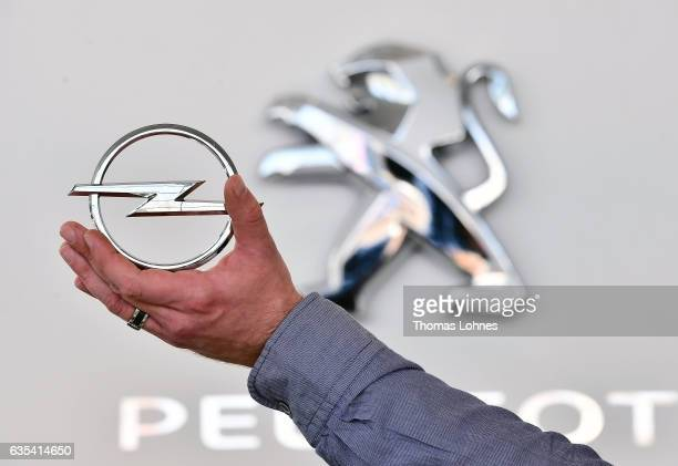 In this photo illustration the Peugeot logo is seen behind an Opel hood ornament on February 15 2017 in Darmstadt Germany PSA Peugeot Citroen is...