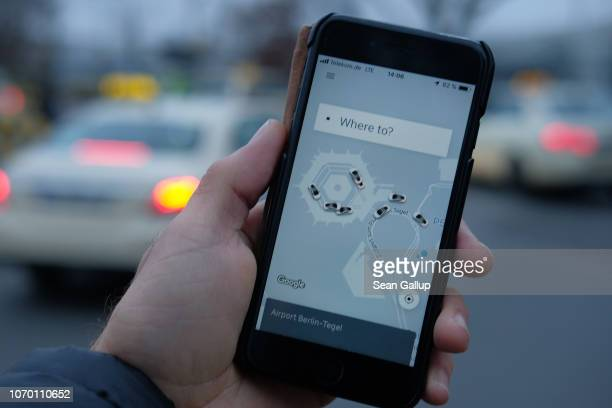 In this photo illustration the photographer holds up a smartphone showing the Uber app and nearby Uber taxis as regular taxis stand behind at Tegel...