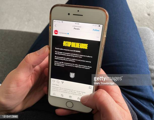 In this photo illustration, the photographer's wife looks at an England Lionesses Instagram post protesting against online abuse on April 30, 2021 in...
