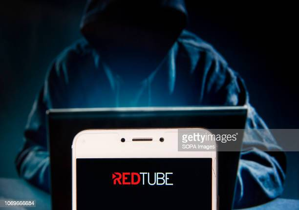 In this photo illustration the Pornographic video sharing site Redtube logo is seen displayed on an Android mobile device with a figure of hacker in...