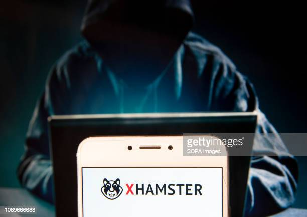 In this photo illustration the Pornographic video sharing site Xhamster logo is seen displayed on an Android mobile device with a figure of hacker in...