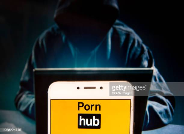 In this photo illustration the Pornographic video sharing website Pornhub logo is seen displayed on an Android mobile device with a figure of hacker...