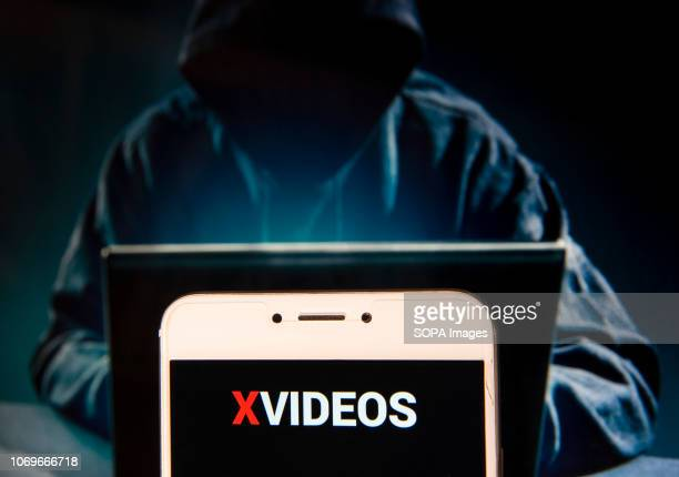 In this photo illustration, the Pornographic video sharing website Xvideos logo is seen displayed on an Android mobile device with a figure of hacker...