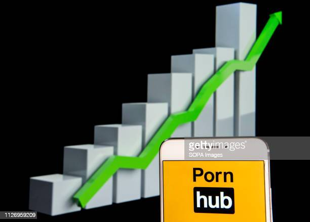 In this photo illustration the Pornographic video sharing website Pornhub logo is seen displayed on an Android mobile device with an ascent growth...