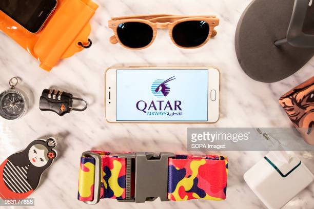 In this photo illustration the Qatar Airways airline logo is displayed on a smartphone screen next to different travel accessories
