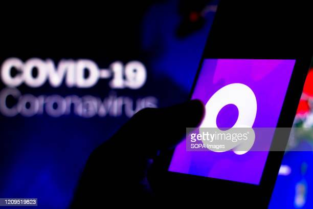 In this photo illustration the Quibi logo seen displayed on a smartphone with a computer model of the COVID19 coronavirus in the background