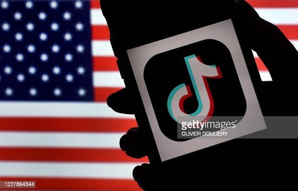 In this photo illustration, the social media application logo, TikTok is displayed on the screen of an iPhone on an American flag background on...