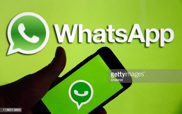 In this photo illustration the social media application logo WhatsApp is displayed on the screen of an iPhone in front of a computer screen showing a...