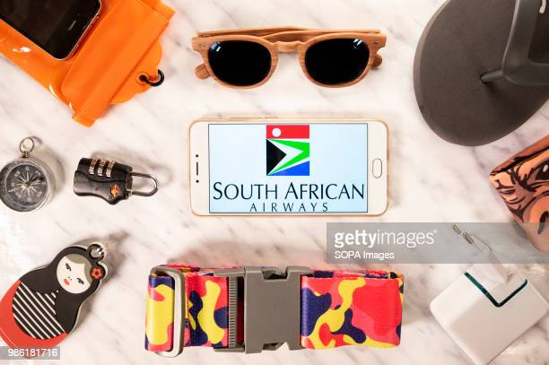 In this photo illustration the South Africa Airways airline logo displayed on a smartphone screen next to travel accessories