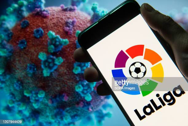 In this photo illustration the Spanish professional football league La Liga logo seen displayed on a smartphone with a computer model of the COVID19...