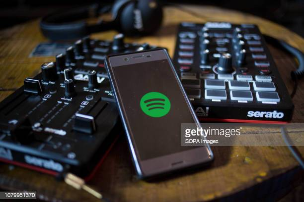 In this photo illustration the Spotify app seen display on an Android smartphone with two Akai controllers AMX and AFX in the background