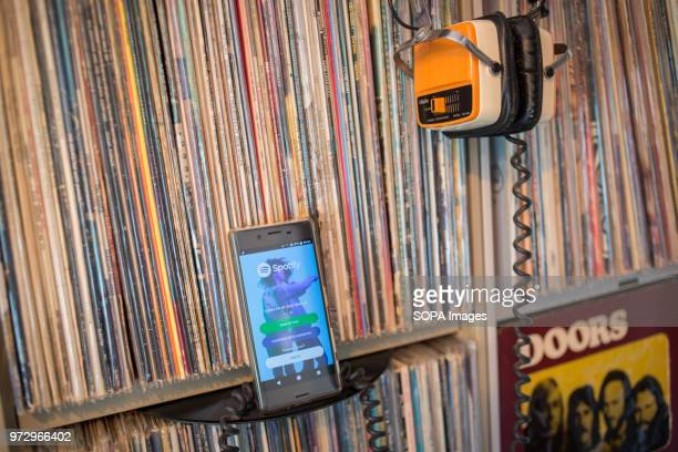 The Spotify application seen display on a Android Sony smartphone front of hundreds of old 33rpm vinyls