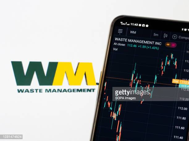 In this photo illustration, the stock market information of Waste Management Inc displayed on a smartphone while the logo of Waste Management Inc...