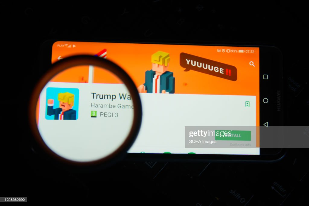 trump wall game app is seen trough a magnifying glass on an