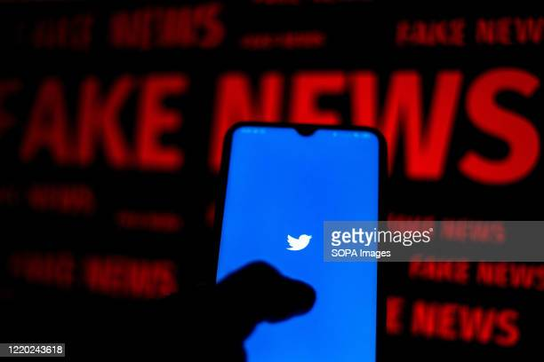 "In this photo illustration the Twitter logo is displayed on a smartphone and a red alerting word ""FAKE NEWS"" on the blurred background."