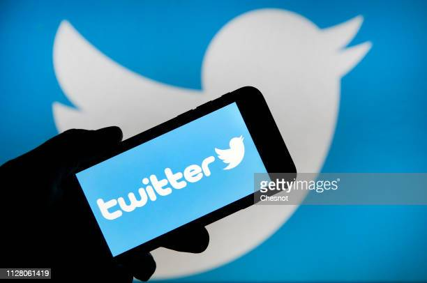 In this photo illustration the Twitter logo is displayed on the screen of an iPhone in front of a computer screen displaying a Twitter logo on...