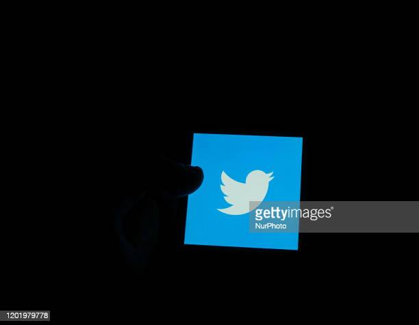 In this photo illustration the Twitter logo is seen displayed on smartphone screen