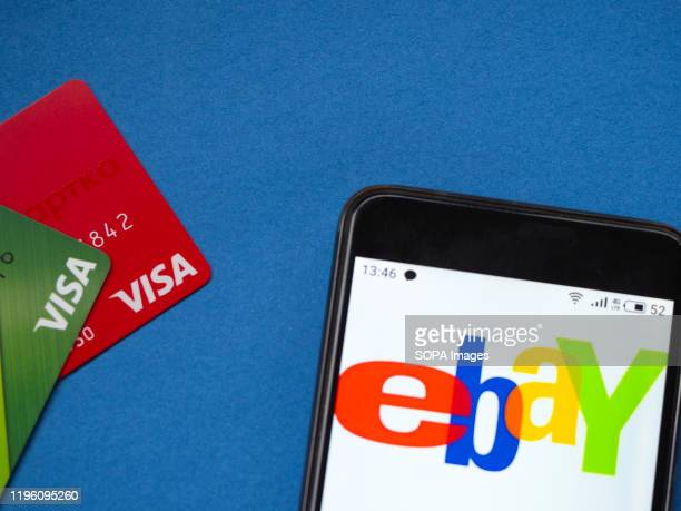 In this photo illustration the Two visa bank cards and a smartphone with eBay logo are seen on a blue background.
