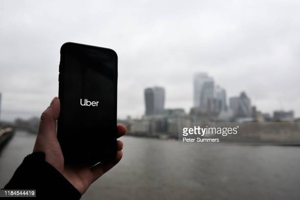 In this photo illustration the Uber logo is displayed on a phone in front of the City of London on November 25, 2019 in London, England. Transport...