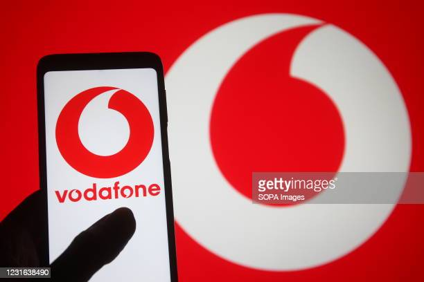 In this photo illustration, the Vodafone logo of a multinational telecommunications company seen displayed on a smartphone into a silhouette of a...