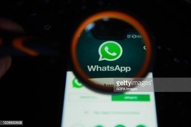 In this photo illustration, the WhatsApp logo is seen trough a magnifying glass on an android mobile phone.