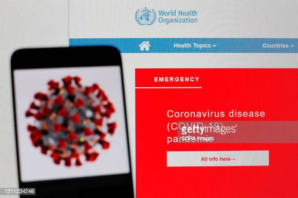 In this photo illustration the World Health Organization web page is seen on a screen of pc and a coronavirus image displayed on a screen of a...