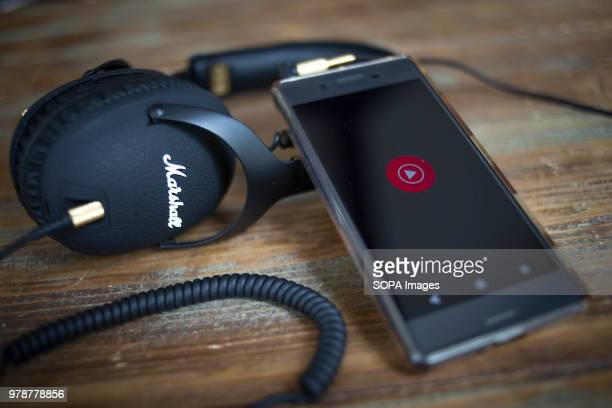 The YouTube Music application seen displayed on a Android Sony smartphone next to a headphone
