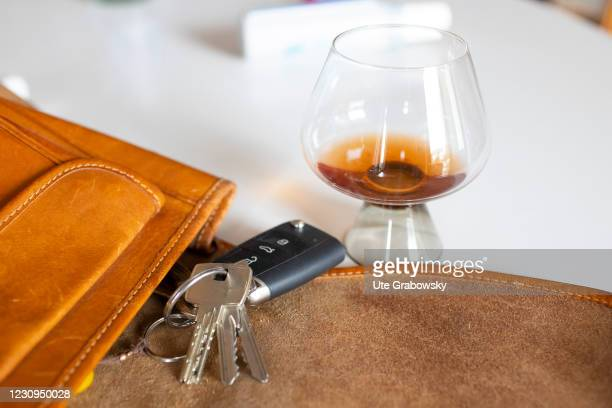 In this photo illustration there is a drink containing alcohol next to a handbag with a car key on February 03, 2021 in Bonn, Germany.