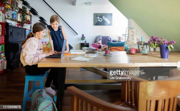 In this photo illustration two girls are doing schoolwork. In times of Corona the children have to learn at home and keep social distance on April...