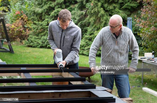 In this photo illustration two men building a substructure for a terrace A metal substructure for a wooden deck on October 27 2018 in Bonn Germany