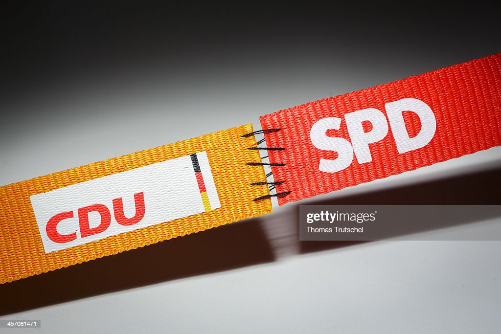 In this photo illustration two ribbons featuring the logos of the Social Democratic Party, SPD and the Christian Democratic Party, CDU, are stitched together, on December 16, 2013, in Berlin, Germany. The CDU and CSU, in coalition with the SPD, will govern Germany for the next four years.