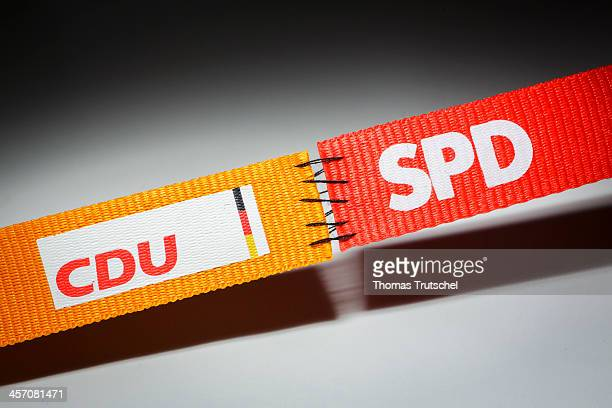 In this photo illustration two ribbons featuring the logos of the Social Democratic Party SPD and the Christian Democratic Party CDU are stitched...