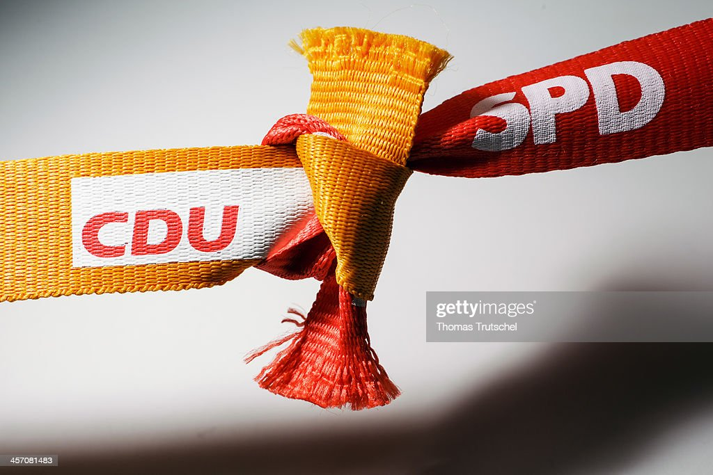 In this photo illustration two ribbons featuring the logos of the Social Democratic Party, SPD and the Christian Democratic Party, CDU, are tied together, on December 16, 2013, in Berlin, Germany. CDU and CSU, in coalition with the SPD, will govern Germany for the next four years.