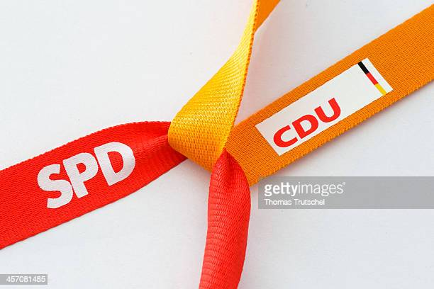In this photo illustration two ribbons featuring the logos of the Social Democratic Party SPD and the Christian Democratic Party CDU are tied...