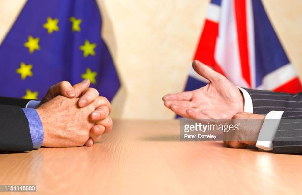 ENGLAND In this photo illustration two sets of hands gesture with a European flag and UK flag in the background shot on October 292019 in...